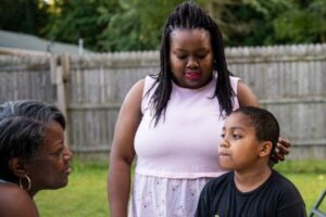 Mom touches 9-year-old son's head while older woman looks on