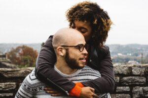 woman kissing bald man's head