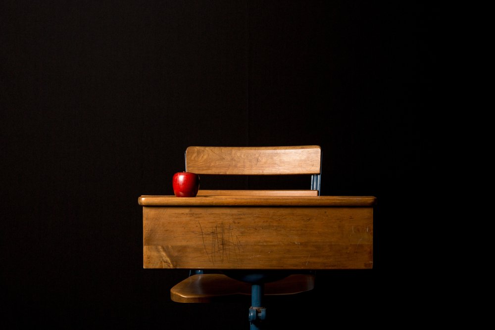 Empty wooden school desk with red apple on top