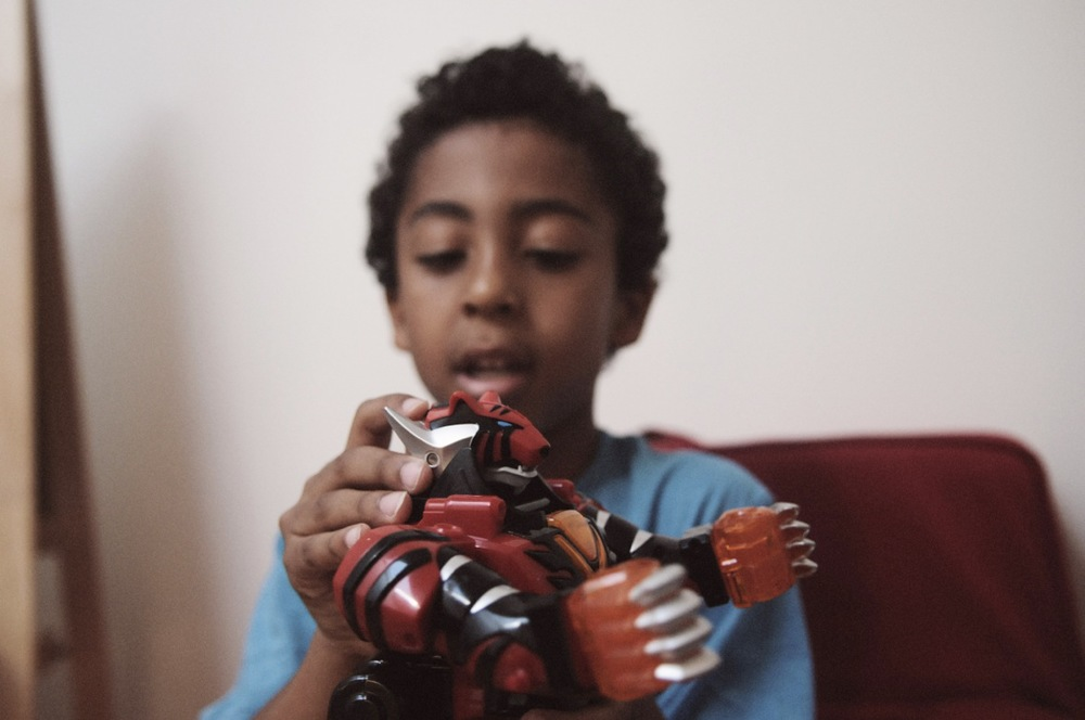Black boy playing with action figure.