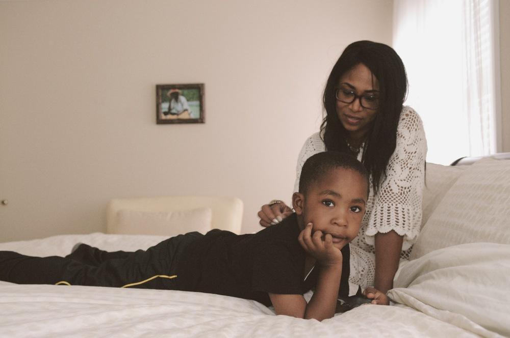 Mom stroking son's back in bed