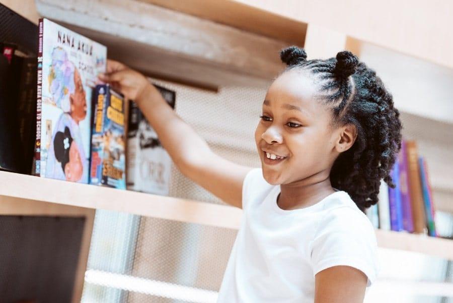 Black girl pulling book from shelf