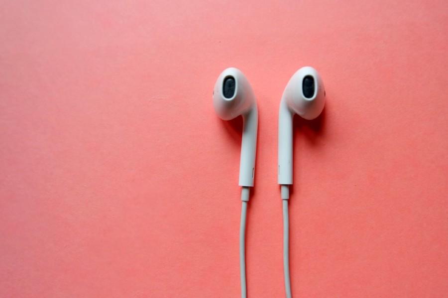 Apple headphones on pink background