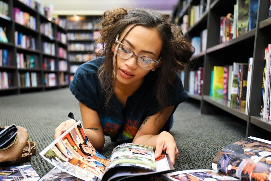 Black teenaged girl wearing glasses reading comics on floor of bookstore