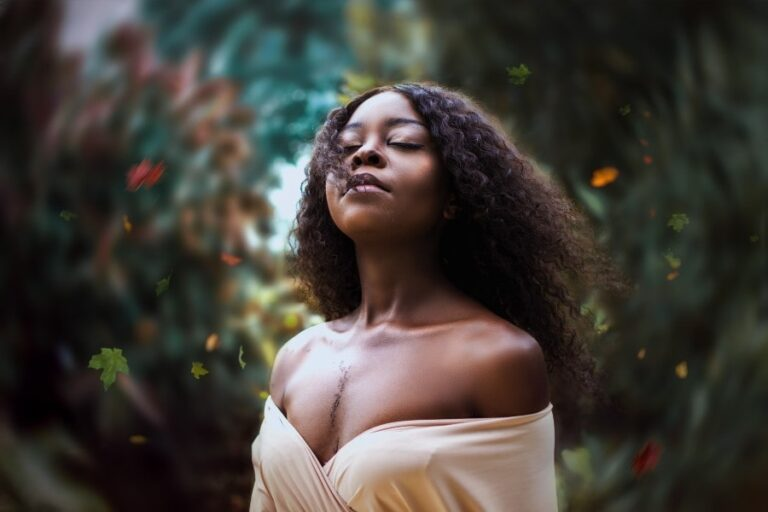 Black woman with her eyes closed and hair blowing in the wind