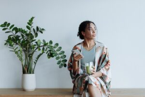 black woman thinking while holding phone and green smoothie